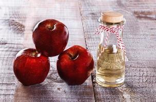 Apfelessig und Äpfel über weißem Holzhintergrund foto