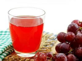 Glas roter Traubensaft mit Früchten