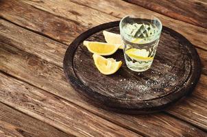 Glas Tequila mit Zitronenscheiben auf einem hölzernen Hintergrund