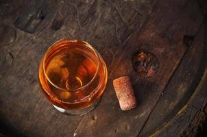 Glas Cognac auf dem Vintage Holzfass