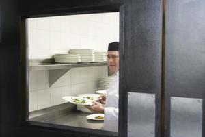 männlicher Koch mit Speisetellern in der Küche foto
