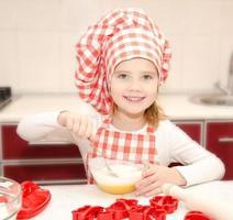 lächelndes kleines Mädchen mit Kochmütze, das Keksteig rührt foto