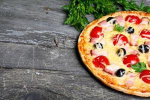 Pizza mit Speck, Oliven und Tomaten foto