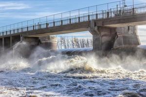 Betonwasserdamm mit aufgewühltem Wasser. foto