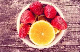 Erdbeeren und Orangen auf Holz foto