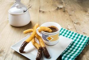 Churros mit heißer Schokolade und Zucker foto