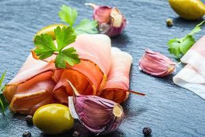 gekräuselte Scheiben köstlichen Schinkens mit Petersilienblättern foto