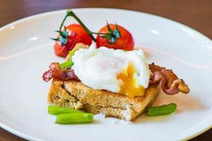 Sandwich mit pochiertem Ei, Parmaschinken und Tomate foto