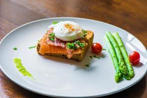 Sandwich mit pochiertem Ei, Parmaschinken und Lachs foto