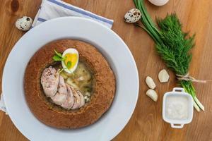 traditioneller weißer Borschtsch mit Wurst, Ei im Brot foto