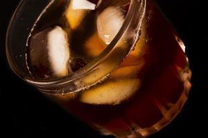 Glas mit dunkler Flüssigkeit voll mit Eiswürfeln foto