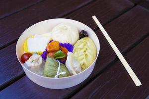 japanisches vegetarisches Essen zum Mitnehmen auf einem dunklen Holztisch foto