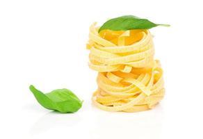 italienisches Nudel-Fettuccine-Nest mit Basilikumblatt foto