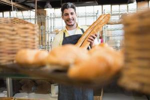 fröhlicher Kellner mit zwei Baguettes foto