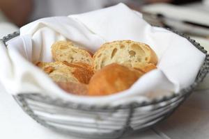 Brot im Korb auf Restauranttisch foto