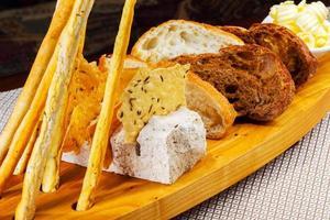 verschiedene Arten von frisch gebackenen Brotlaiben in Holztablett foto