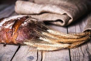 frisches Brot und Weizen auf dem Holz foto