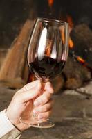 Wein am Kamin, Gläser Wein. Verkostung. Hand. foto