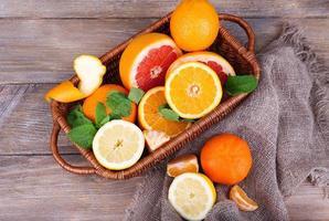 frische Zitrusfrüchte mit grünen Blättern auf hölzernem Hintergrund foto