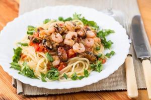 Pasta mit Meeresfrüchten und Weißwein auf Serviette foto