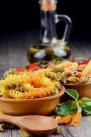 rohe Eliche und Penne Tricolori Nudeln in den Holzschalen foto