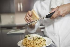 Koch reibt Käse auf Nudeln in der Küche foto