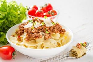 Pasta Bolognese in weißer Schüssel mit Salat und Tomaten foto
