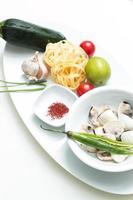 Knoblauchzehen mit ungekochten Nudeln, Safran, Jakobsmuscheln, Limette, Zuc foto