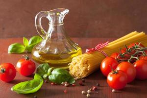 rohe Nudeln Olivenöl Tomaten. italienische Küche in rustikaler Küche foto