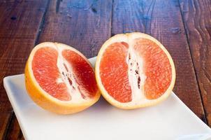 rosa Grapefruit geschnitten in halben quadratischen Platte alten Holztisch foto
