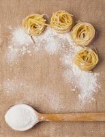 Nudeln und Holzlöffel mit Mehl auf Entlassung foto