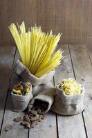 verschiedene Formen von Nudeln in Jutesäcken auf Holztisch foto