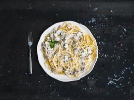 Nudelspaghetti mit cremiger Pilzsauce und Basilikum in Weiß foto