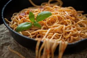Linguine mit Basilikum und roter Sauce in gusseiserner Pfanne foto