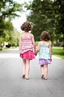 zwei glückliche Schwestern, die Hände halten und nach draußen gehen foto