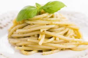 italienische Pasta Spaghetti mit Pesto-Sauce und Basilikumblatt