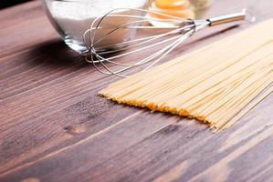 rohe Nudeln mit Gewürzen und Zutaten brauner Holztisch foto