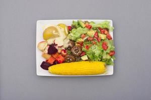 Salat mit Avocado und Tomate mit Kartoffeln, Wurzelgemüse und Mais
