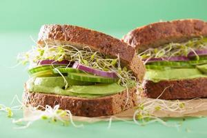 gesundes Roggensandwich mit Avocado-Gurken-Luzerne-Sprossen foto