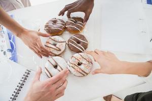 Geschäftsleute, die Donut am Schreibtisch nehmen foto
