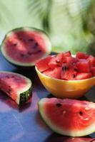 Wassermelonenstücke in einem gelben Teller und Scheiben auf dem Tisch foto