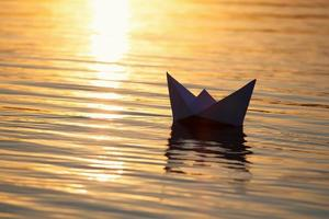 Papierboot segeln auf dem Wasser mit Wellen und Wellen foto
