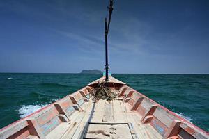 blaues Fischerboot, das zum Meer hinausgeht foto