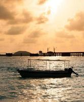 Fischtrawler auf dem Wasser und dramatische Wolken bei Sonnenaufgang