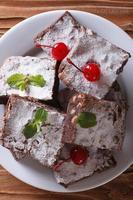 Brownies mit Minze und Kirschen auf Teller. vertikale Draufsicht