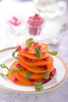 Salat aus Rucola, Persimone, Granatapfel foto