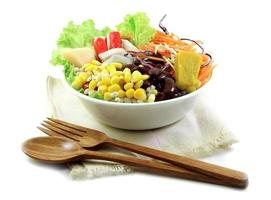 Salat und Holzlöffel, Gabel auf Stoff foto
