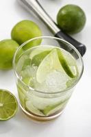 Caipirinha mit Eis und Limette in einem Glas foto