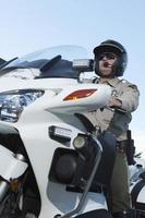 Verkehrspolizist sitzt auf Fahrrad gegen Himmel foto