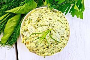 Butter mit Spinat und Kräutern in einer Schüssel auf einem leichten Brett foto